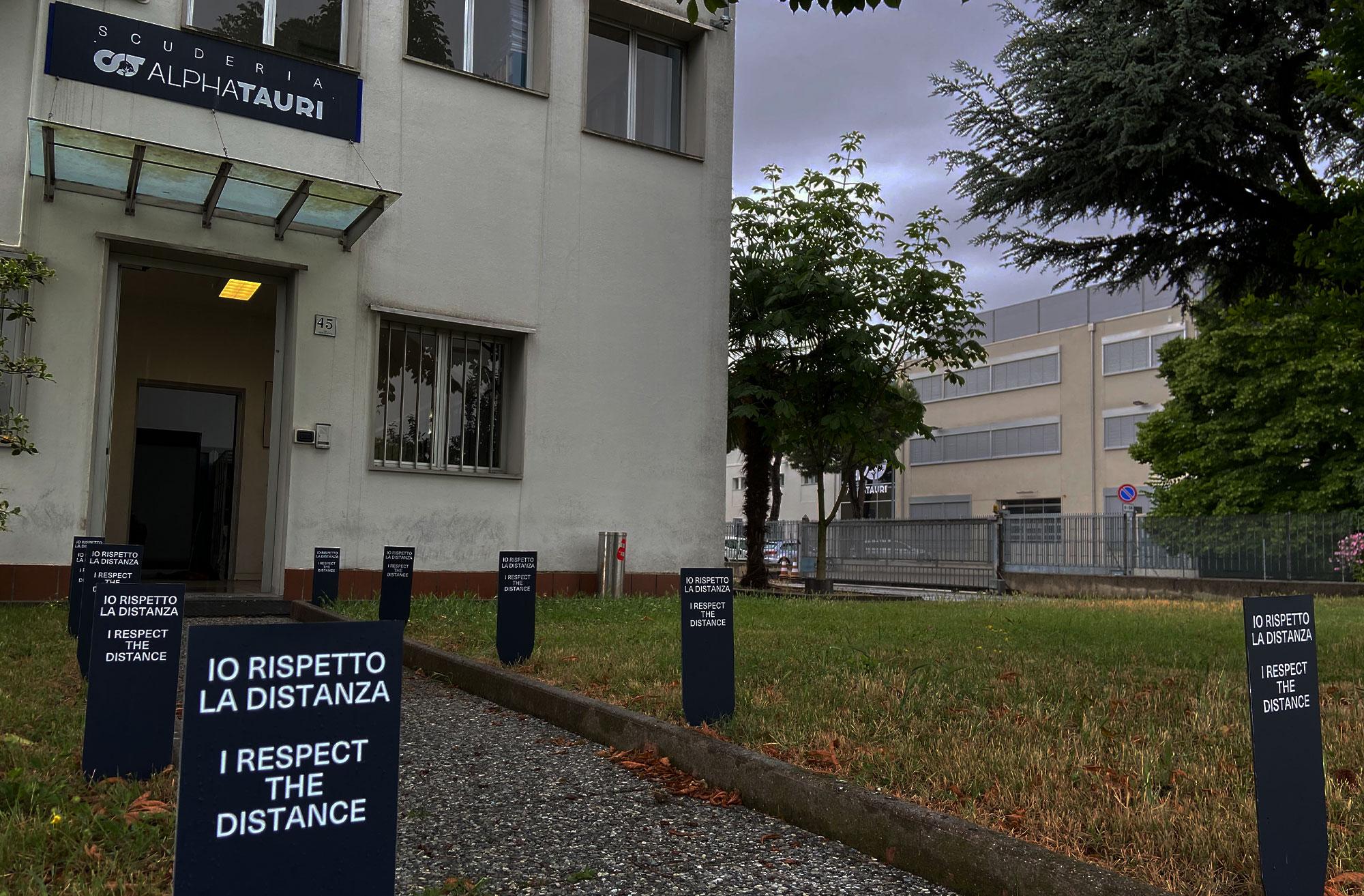 """A faenzai központ előtt egymástól megfelelő távolságra elhelyezett, """"Tisztelem a távolságot!"""" felirattal ellátott táblák figyelmeztetik a dolgozókat a védőtávolság tartására. <br /><br />Fotó: Alpha Tauri"""