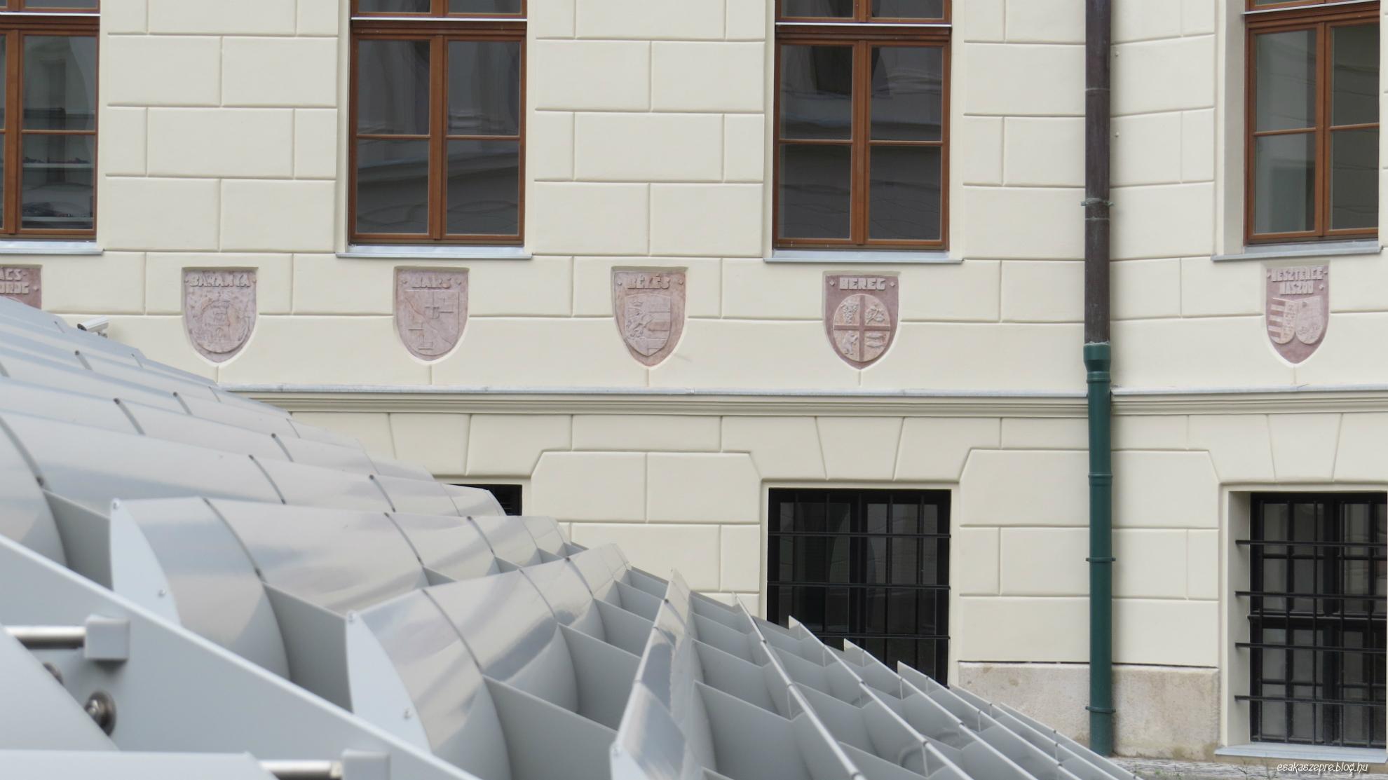 Az udvari homlokzaton körben az építéskori vármegyék címerei