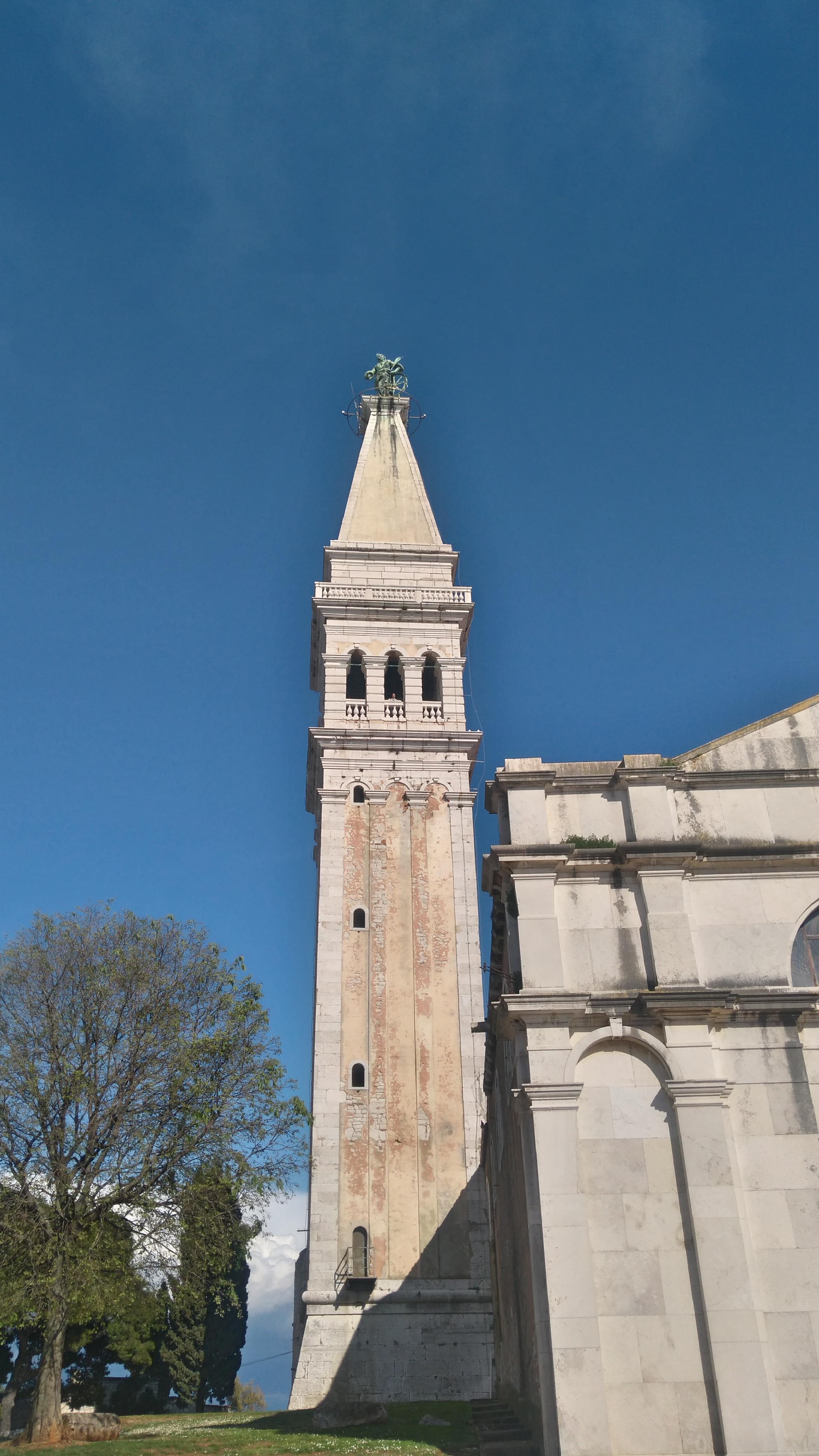 a templom tornya, tetején a város védőszentjének szobrával
