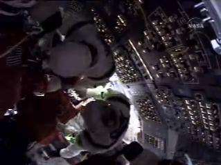 Az űrhajósokat besegítik a székeikbe.