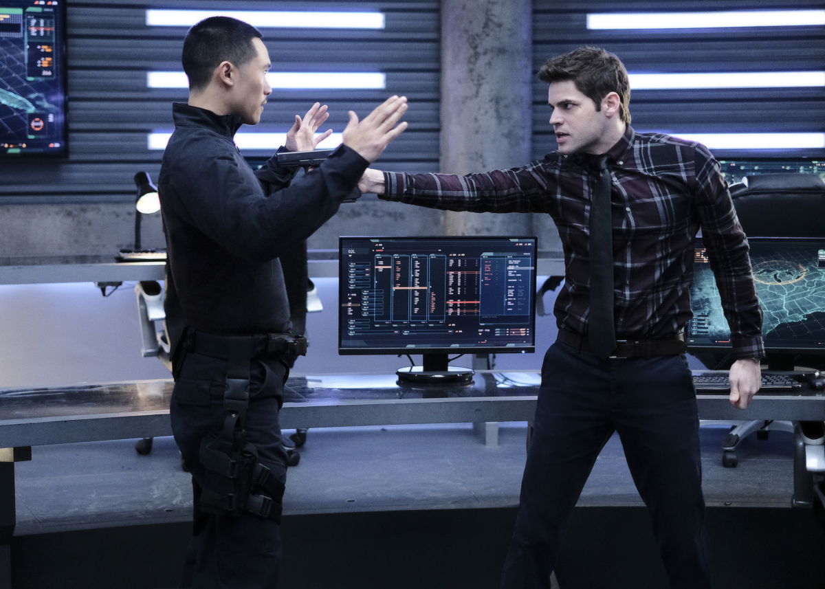 Supergirl -- 'In Search of Lost Time' -- Image Number: SPG315a_0334.jpg -- Pictured (L-R): Curtis Lum as Agent Demos and Jeremy Jordan as Winn -- Photo: Robert Falconer/The CW -- © 2018 The CW Network, LLC. All Rights Reserved.