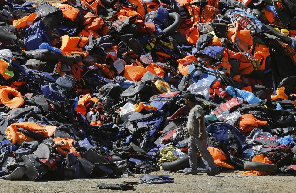 Helyi lakos szemléli a menekültek által a parton hagyott mentőmellényeket és felfújható eszközöket  a görög Leszbosz-on. (f.: Reuters)