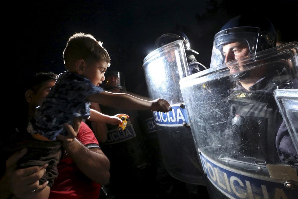 Menekült férfi tartja a rendőrök elé gyermekét a horvát-szlovén határon. (f.: Reuters)