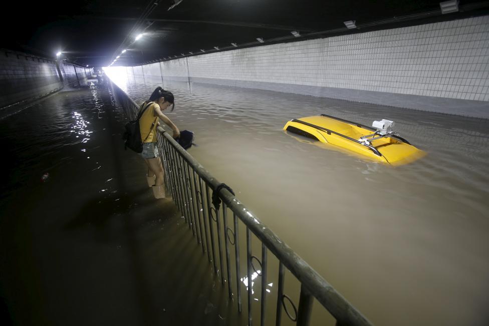 Kínai nő próbál átjutni a heves esőzések során víz alá került alagúton. (f.: Reuters)