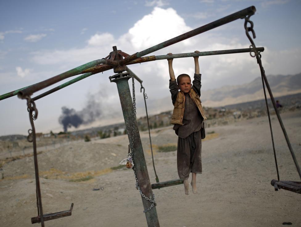 Egy afgán kisfiú lóg egy Kabul melletti körhintán, miközben háta mögött robbanás okozta sűrű füst gomolyog. (f.: Reuters)