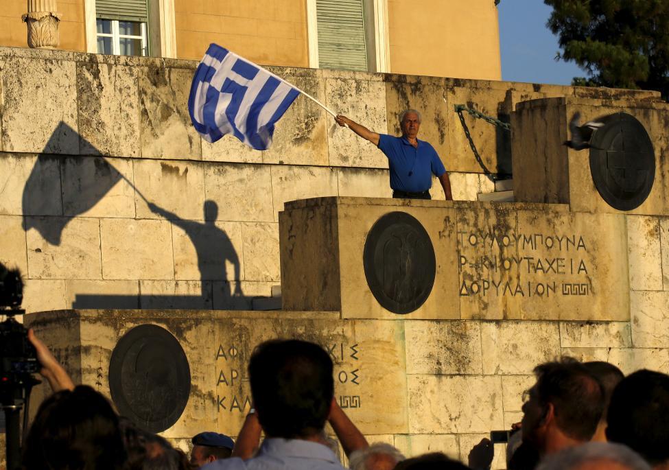 Egy tüntető lengeti a nemzeti zászlót a görög parlament épülete előtt összegyűlt tömegnek, akik azért gyűltek össze, hogy kényszerítsék a kormányt, kössön egyezséget nemzetközi hitelezőivel, és biztosítsa az ország gazdasági jövőjét. Az euróövezeti országok állam- és kormányfői hétfőn találkoznak újfent, hogy megvitassák Görögország új javaslatait az adósságválság ügyében - miközben egyre több elemző látja közeledni az ország kilépését az eurózónából. (f.: Reuters)