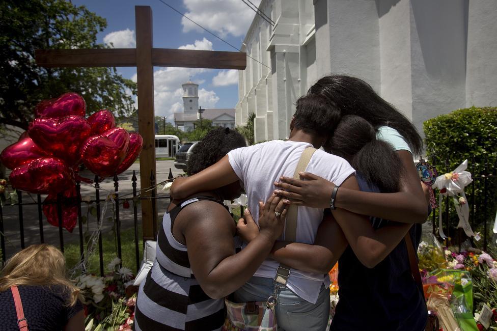 Egy áldozat családtagjai gyászolnak a dél-karolinai Charleston egyik temploma előtt, ahol szerda este a 21 éves Dylann Roof 9 afro-amerikait lőtt le a templomban tartott szertartás alatt. A férfit az FBI az eset után nemsokkal őrizetbe vette, tettéért halálra is ítélhetik. (f.: Reuters)