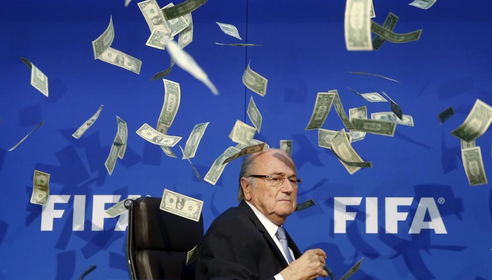 Sepp Blatter FIFA elnököt dobálják meg bankjegyekkel, utalva az őt és az általa vezetett szervezett körüli korrupciós botrányokra. (f.: Reuters)
