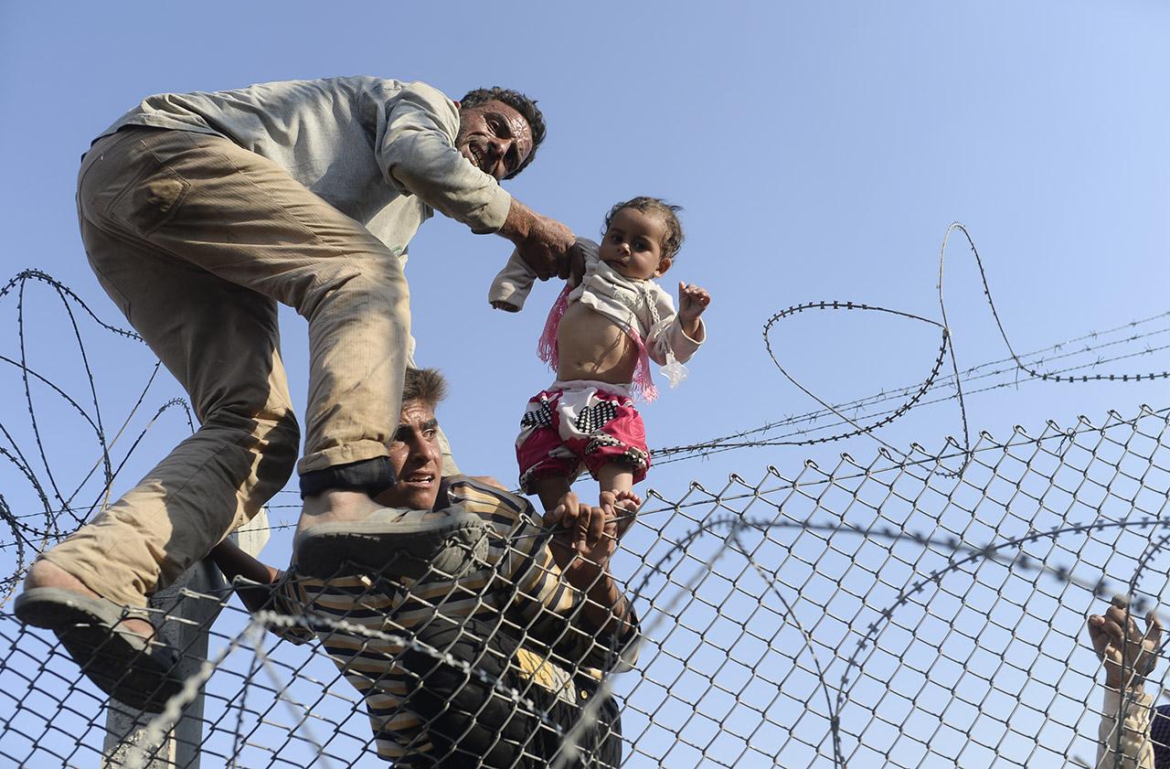 Szíriai menekültek másznak át a török-szír határon emelt kerítésen, hogy az országban zajló polgárháborútól messzebbre kerülhessenek. (f.: AFP)