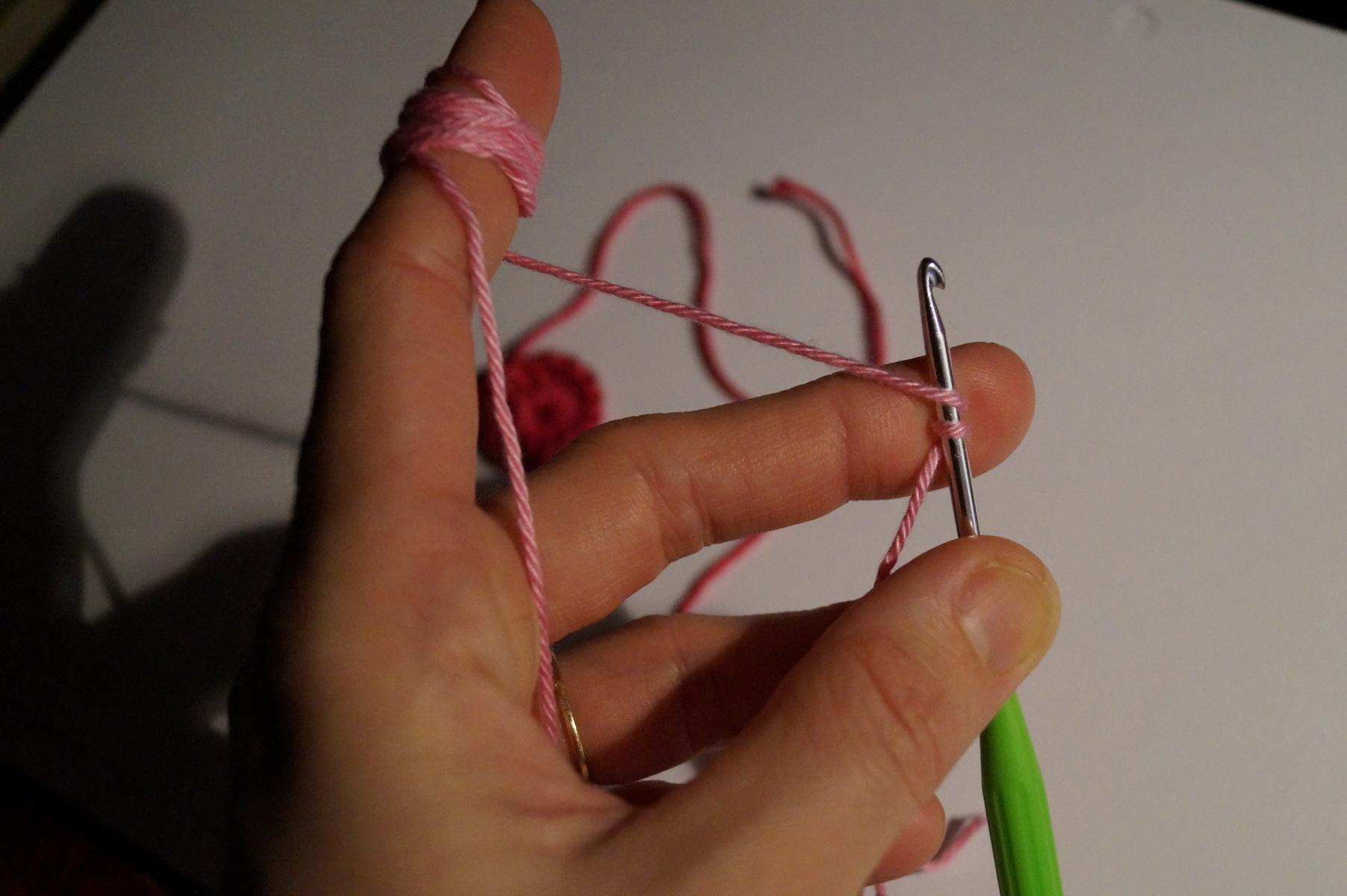 A következő kört 'standing double crochet'-val, magyarul kb. 'álló egyráhajtásos pálcával' kezdjük, ehhez először is kétszer rátekerjük a fonalat a tűre.
