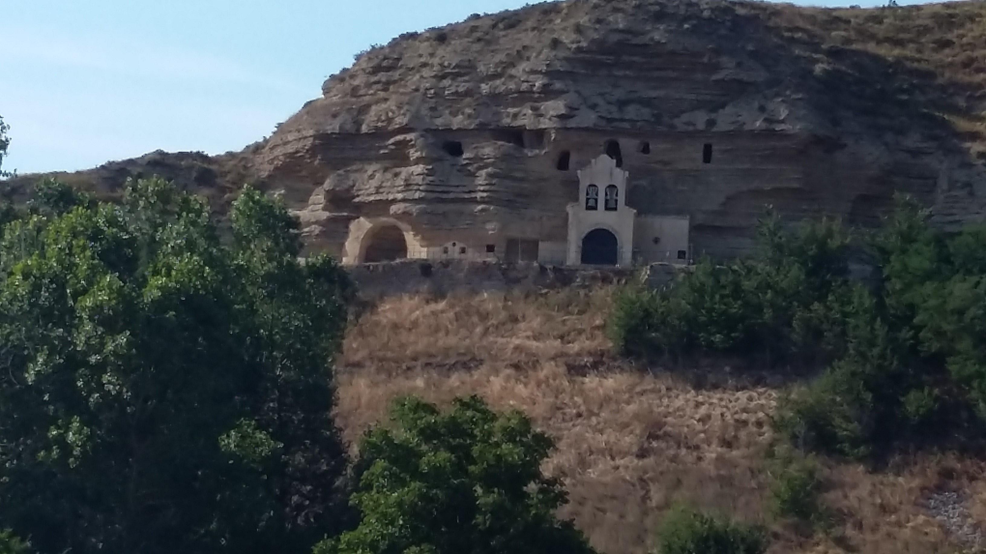 Villafranca Montes de Oca. Szerzetes barlangok és a templomuk a hegyoldalban.