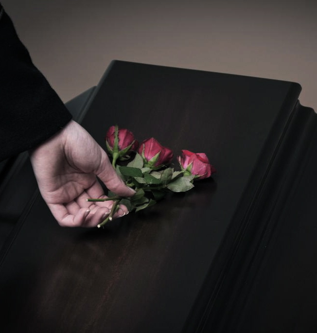 person-placing-roses-on-casket-top.jpg