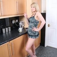Nagy mellű érett anyuka a konyhában dohányzik meztelenül