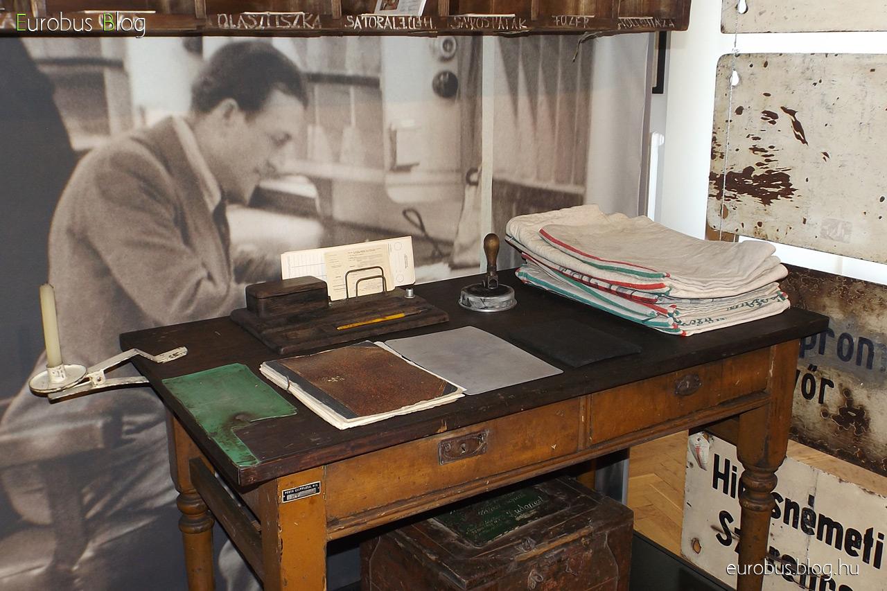 Kis fa íróasztal, rajta jutazsákokkal, bélyegzővel és gumialátéttel, iratokat tartalmazó mappával. Fölötte a fakkok.