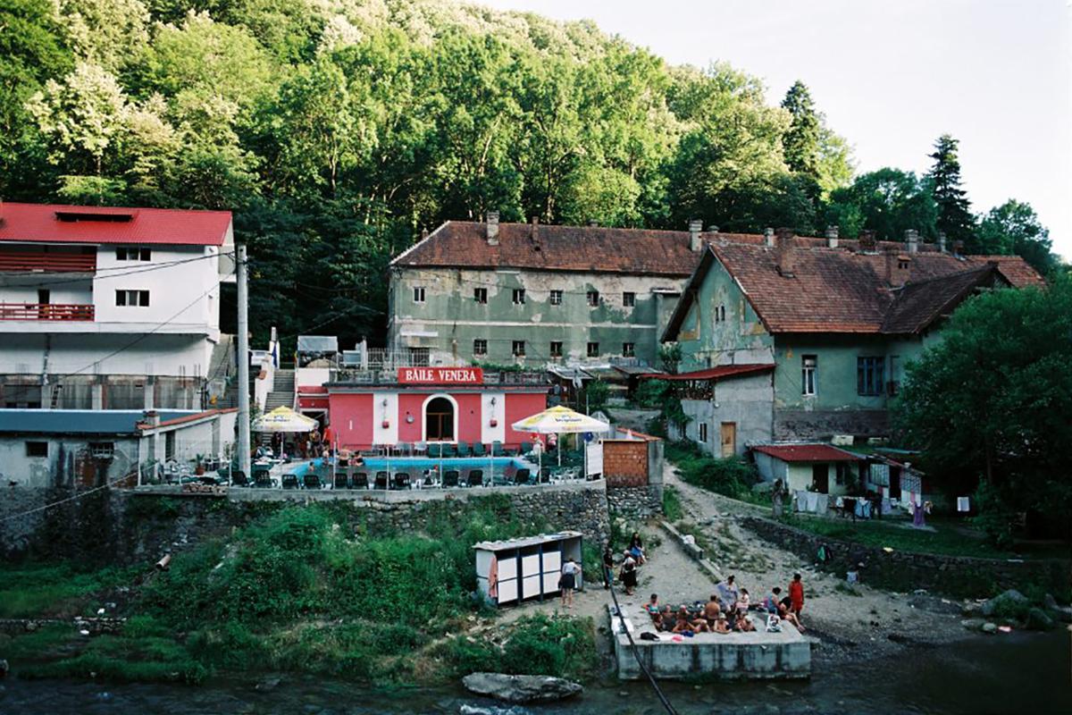Balkán a köbön. A háttérben a bezárt Ferenc-fürdő. Elől a Cserna partján összetákolt kabinok, öltözők. Balra szennyvíz folyik a folyóba, de ez a fürdőzőket nem zavarja. (Fotó: Reptilianul.ro Isabelle Vinteuil)