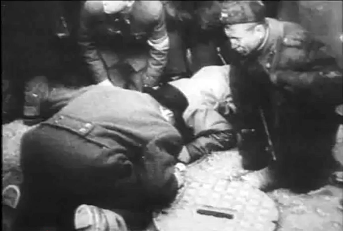 Korabeli filmfelvétel, hogy a forradalom napjaiban a felkelők a lenti kopogásokat hallgatják a Köztársaság téren.