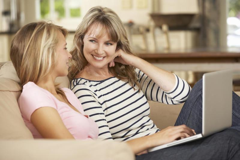 m_e-com-filha-adolescente-que-senta-se-em-sofa-home-using-laptop-55894787.jpg
