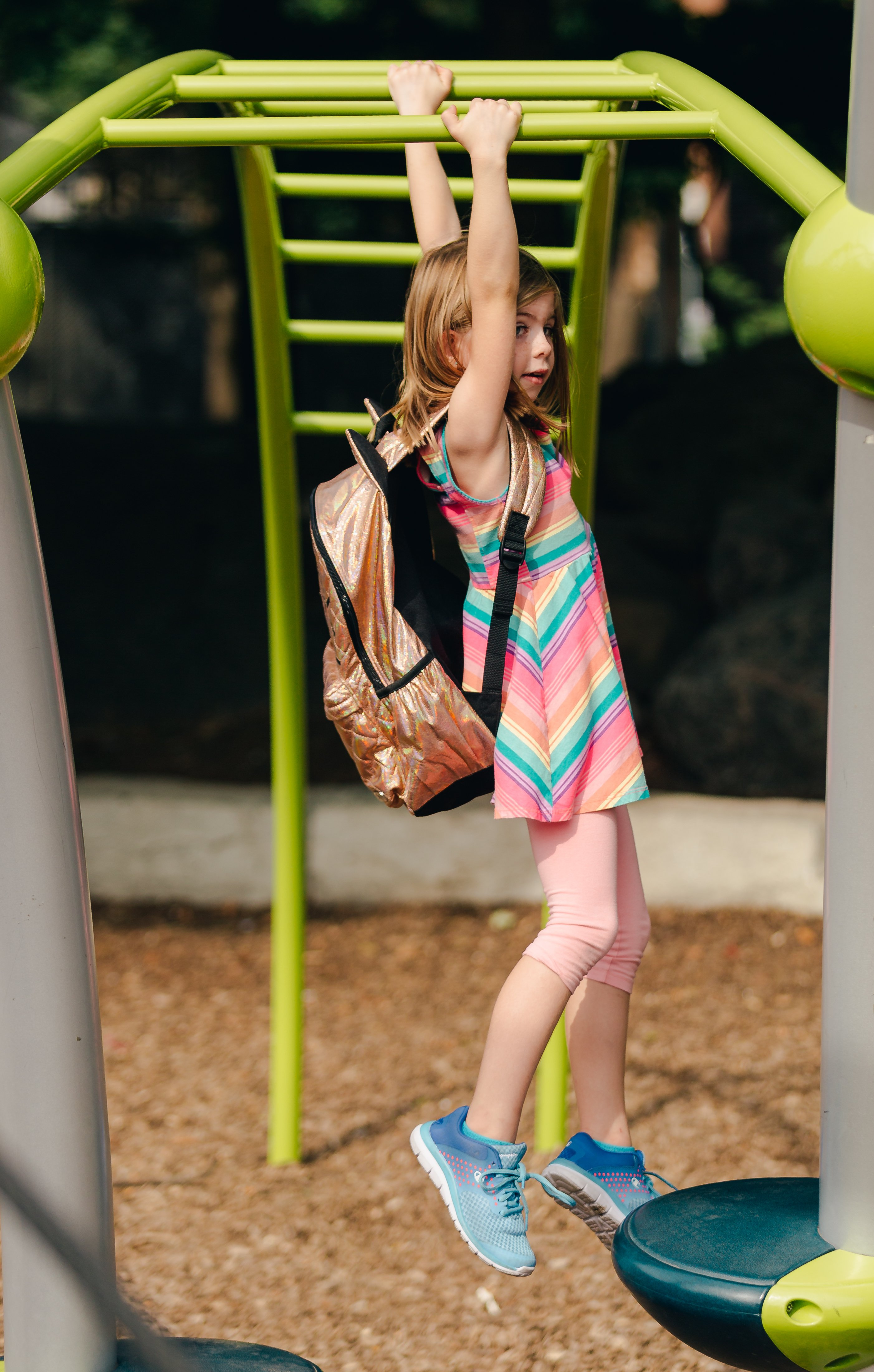 young-girl-swinging-on-bars-with-backpack_4460x4460.jpg