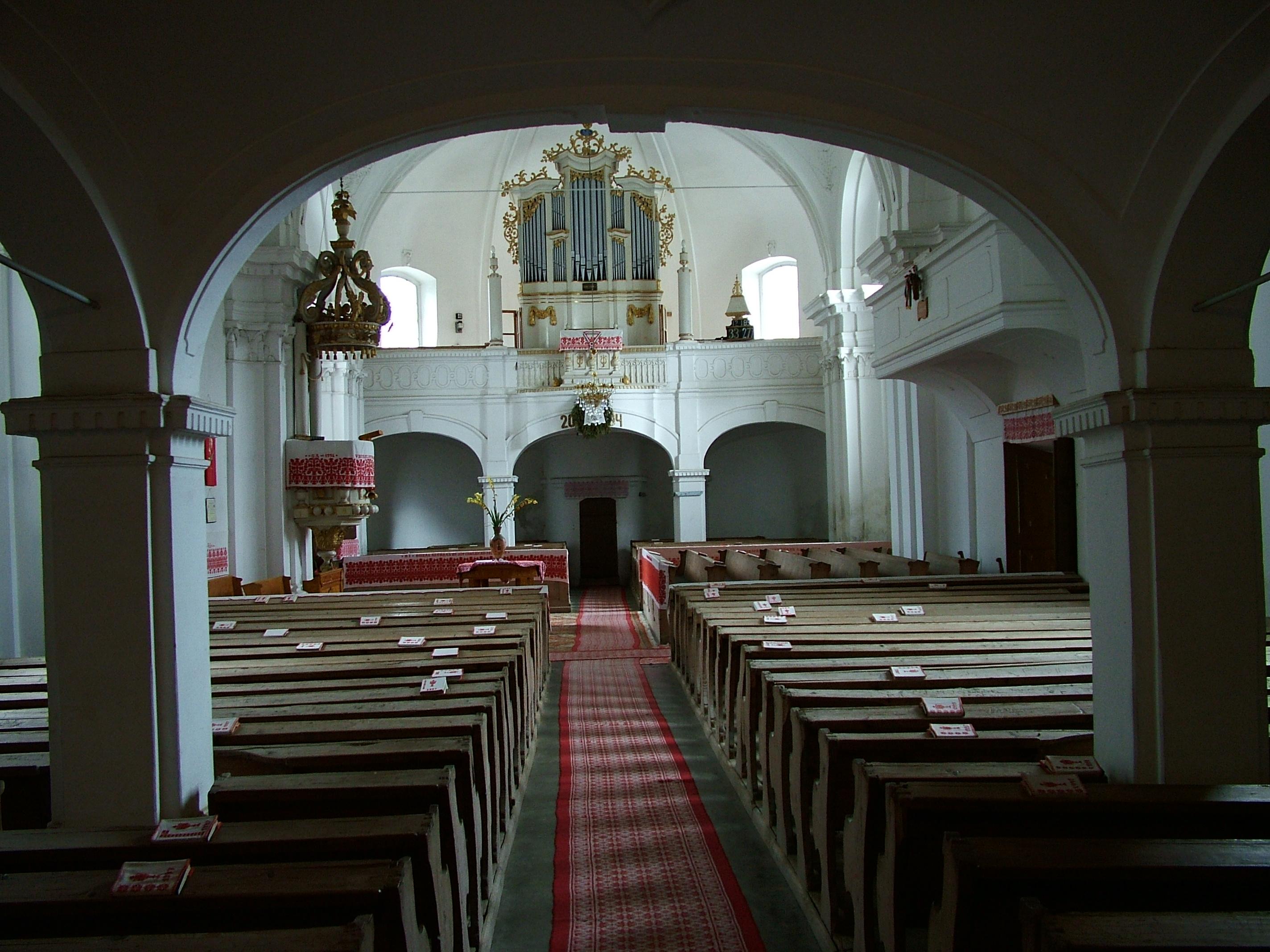 Az unitárius templombelső, szép piros varrottasokkal.