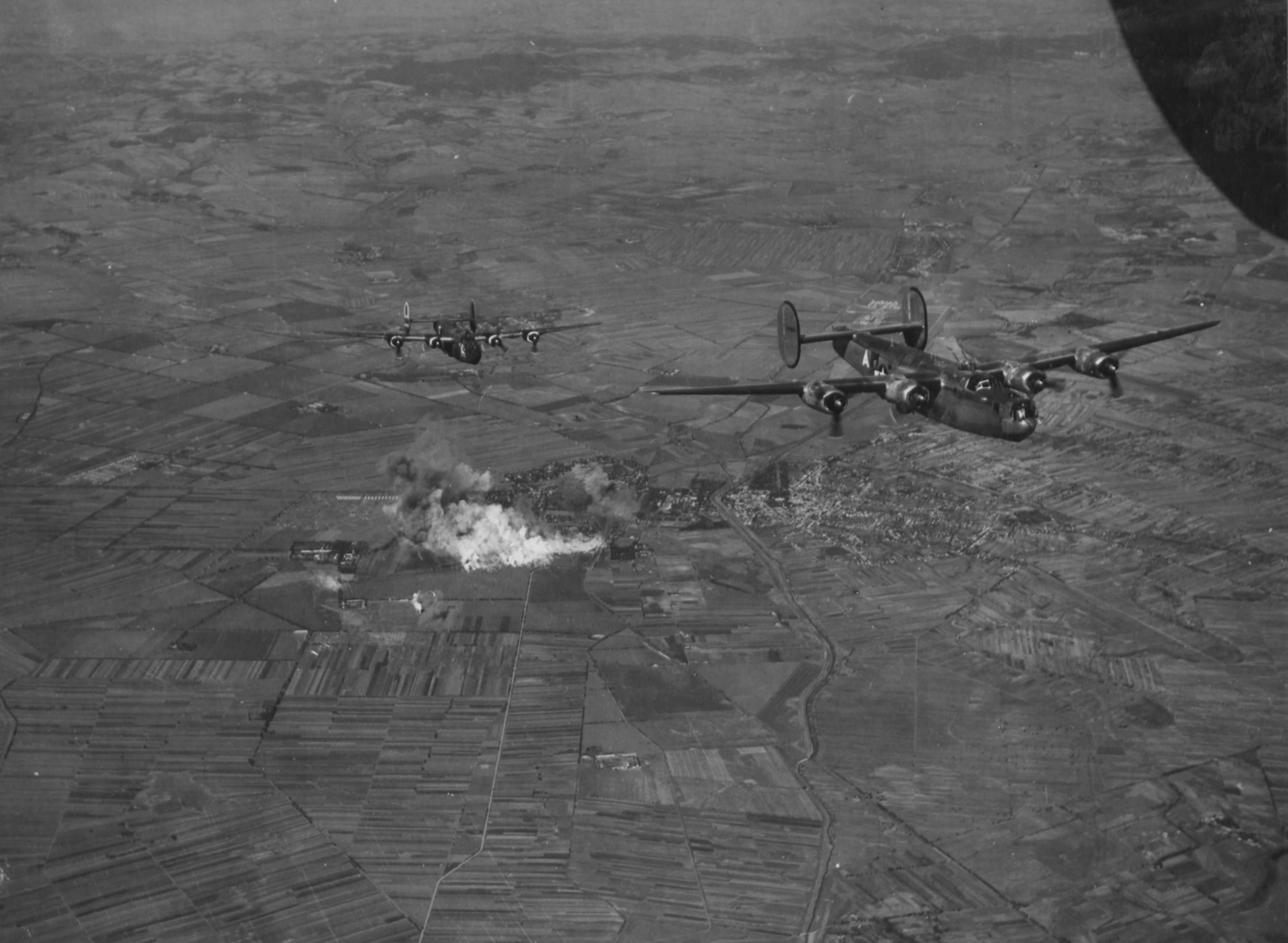 A lángoló vasúti pályaudvar és újhatvani városrész légi felvételről. (USA NA / USAAF szabad hozzáférésű archívuma)
