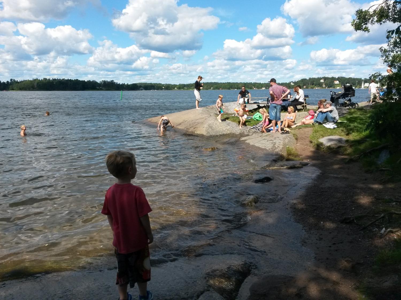 Egy kisfiú biztos távolból figyel meg egy fürdőző családot Stockholm közelében, Vaxholm szigetén (2015.nyár, levegő hőmérséklete 25 fok, a tenger vízé pedig nem túl sok. - (Fotó: Szabó Vivien)