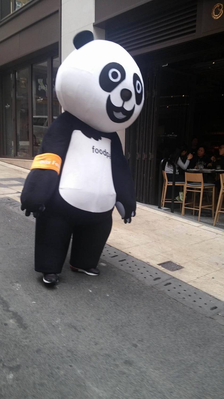 Ételfutár szolgálat. Foodpanda a hálózat neve, úgy népszerűsíti magát, hogy ezek a panda jelmezes emberek meglepetésszerűen felbukkannak a város különböző pontjain. - (Fotó: Pataki Niki)