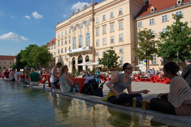 Sörözés – Ausztriában szabad alkoholt fogyasztani az utcán. Ezért sűrűn látni olyan fiatalokat, akik elfogadható áron veszik meg a sörüket egy közeli szupermarketben, majd elfogyasztják azt a város valamelyik kellemes piacterén, ahol egy padon vagy simán csak a földön foglalnak helyet. (piactér, Bécs) - (Fotó: Laslavic Tímea)
