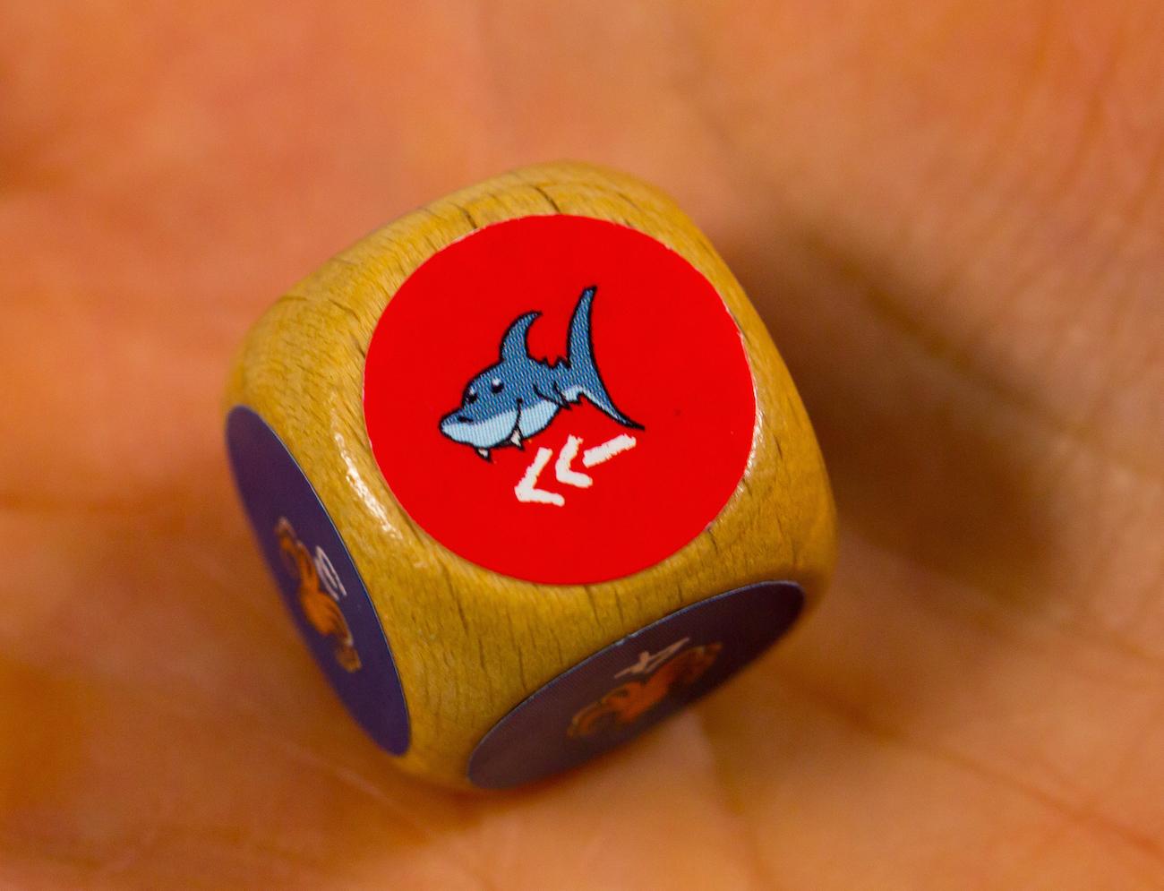 Két uszonyos cápa: a tábla forgatható cápája két mezővel arrébb vándorol.