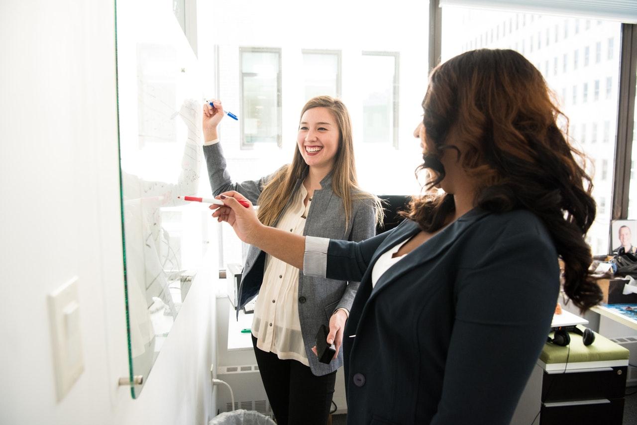 two-women-in-front-of-dry-erase-board.jpg