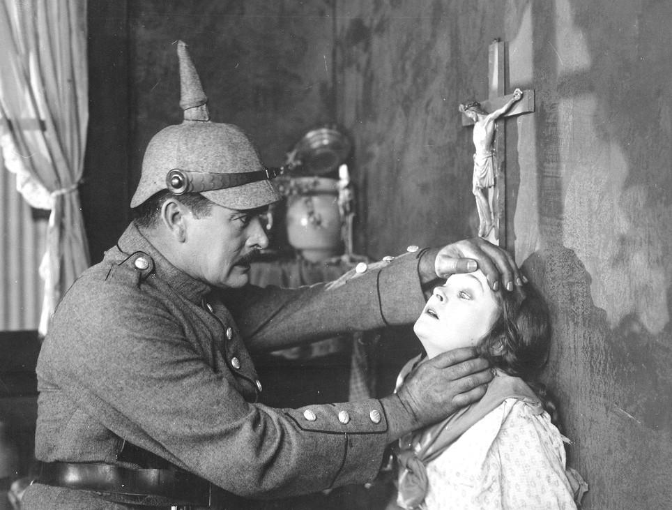 Brutális germán katona egy belga szűzzel erőszakoskodik. A feszület alatt természetesen, mert ott esik igazán jól. Jelenet egy amerikai propagandafilmből.