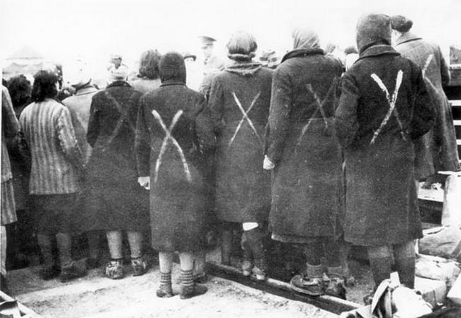 A Ravensbück-i koncentrációs táborból elszállításra váró női foglyok. Akinek nem jutott csíkos ruha, azt egy fehér kereszttel jelölték meg.