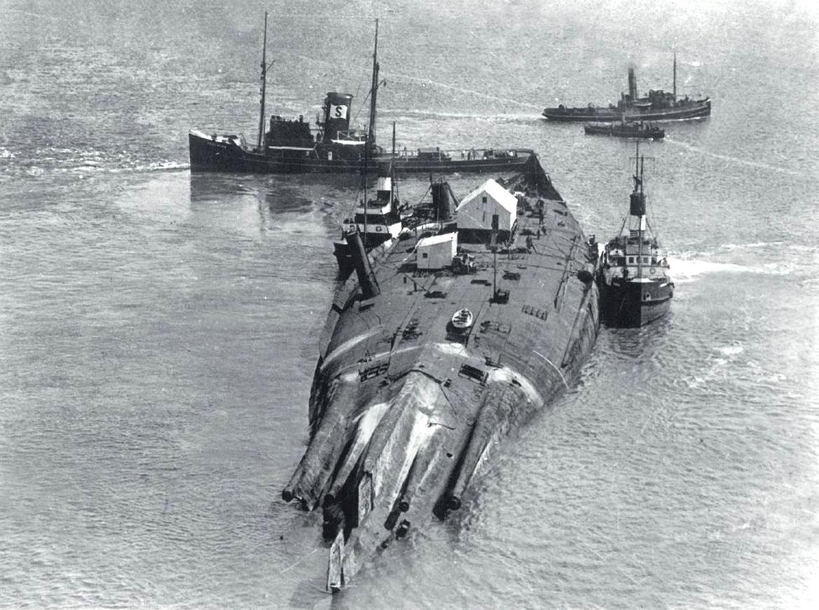 A kiemelt, felborult Moltke csatacirkálót a bontóba vontatják.