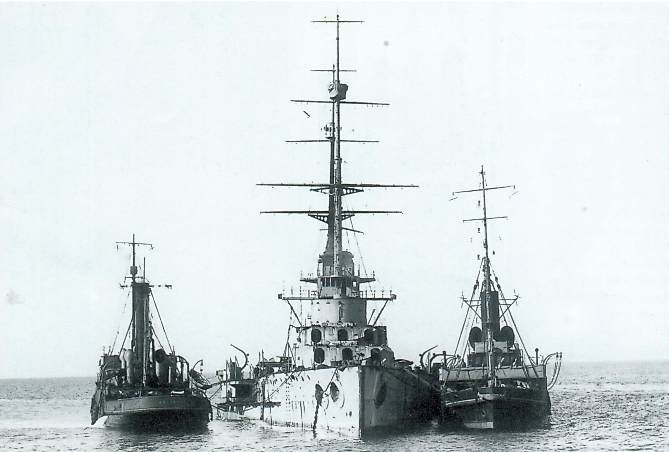 A megsüllyedt csatahajó, a mellette álló vontatókkal.