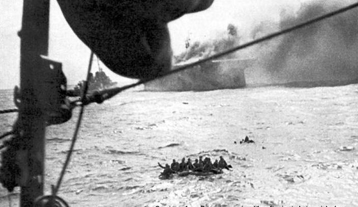 A rombolók felveszik az anyahajó mentőtutajokon menekülő tengerészeit.