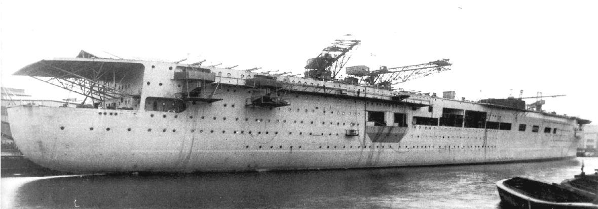 A hajógyári mólónál álló, felszerelés alatt álló anyahajó.