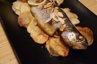 Sült pisztrángok pirított mandulával, burgonya chips ágyon