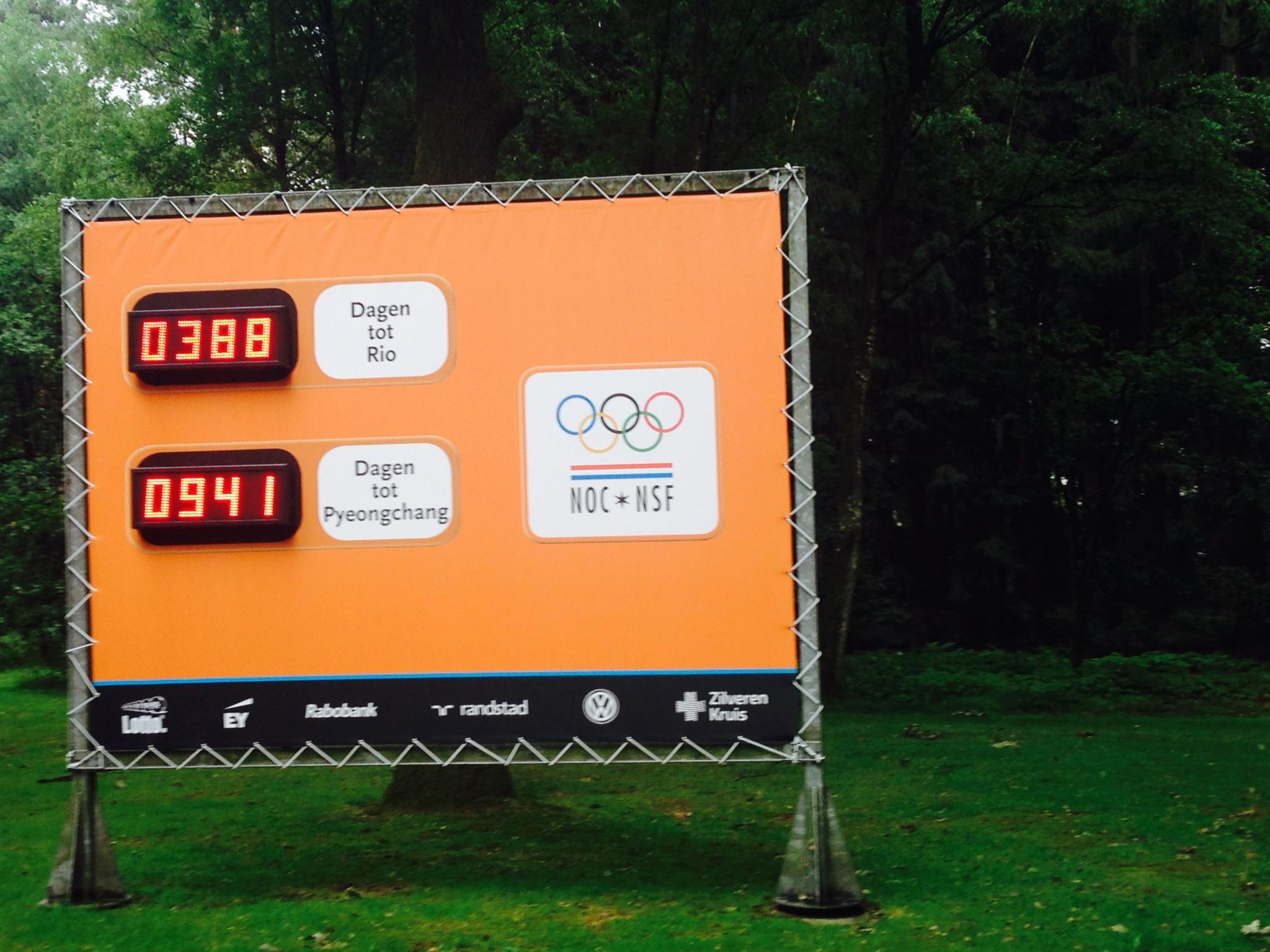 Az olimpiai falu bejárata, táblán kiírva a közelgő események..