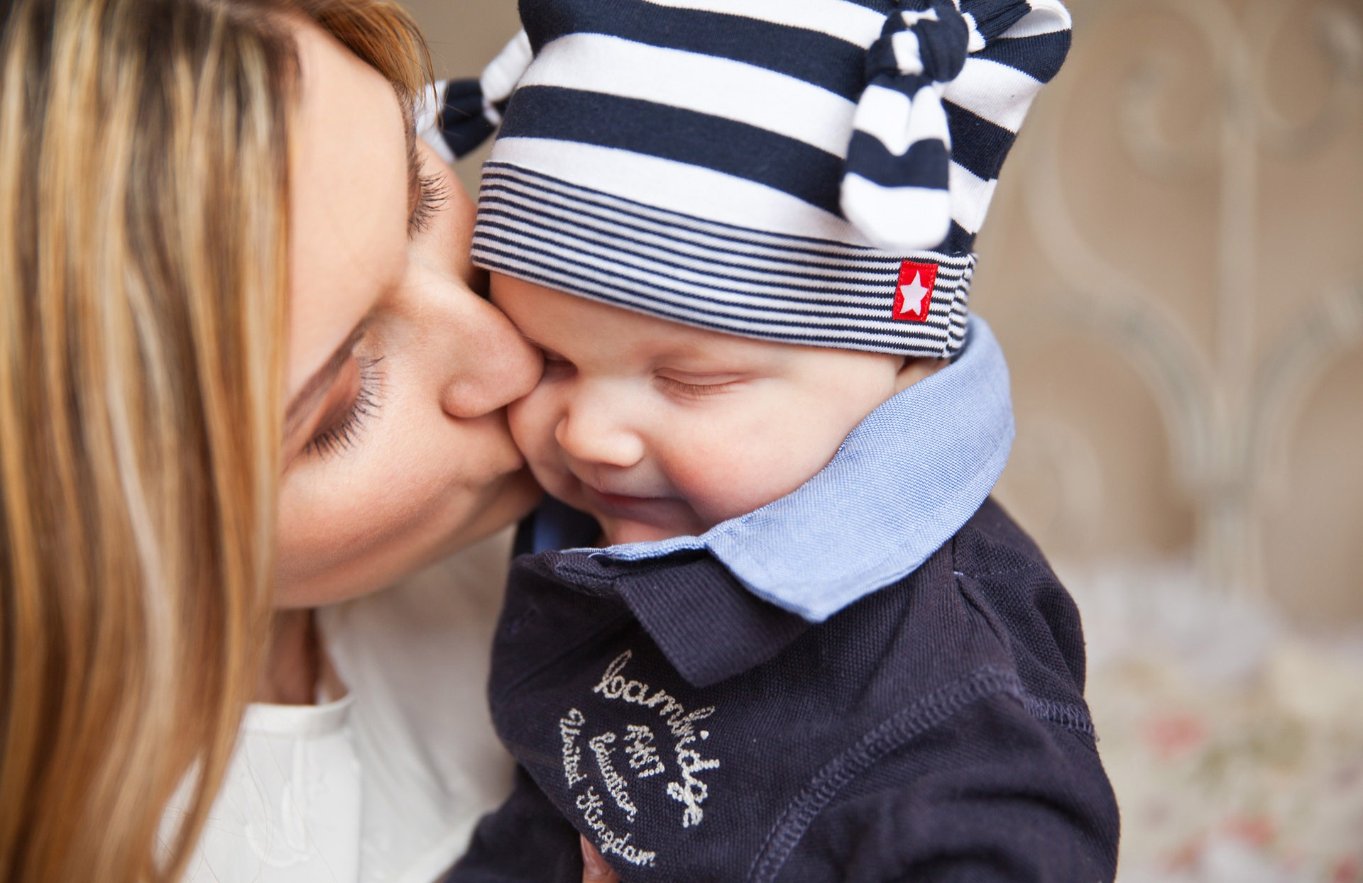 canva_woman_in_white_shirt_kissing_baby_with_black_and_white_stripe_knit_cap.jpg