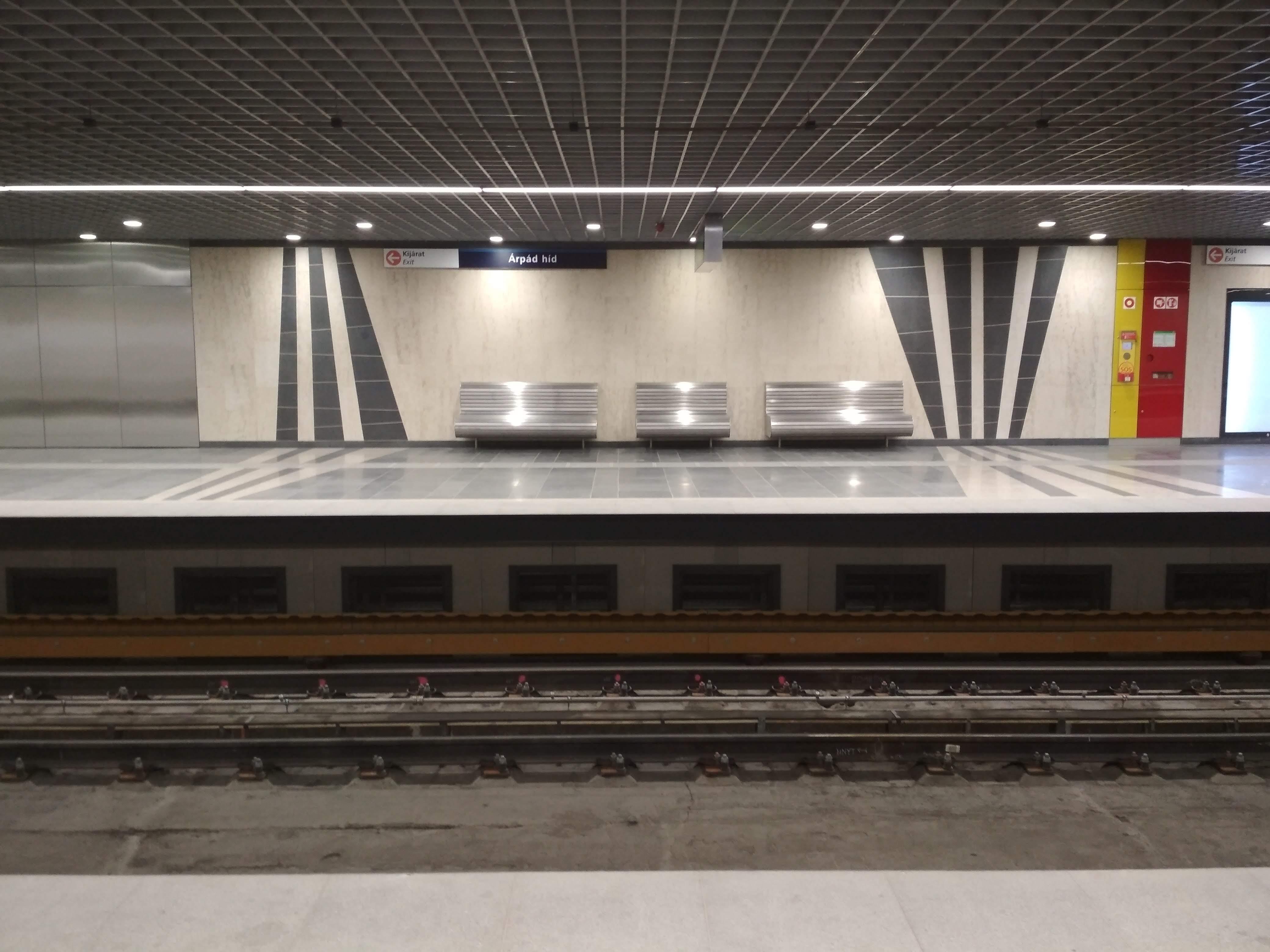 A padló és a falak burkolatai tartósságot sugallnak, és a rozsdamentes acél padok is jól mutatnak az állomáson. A falra felfutó burkolati minták szerintem nem sokat adnak hozzá az állomás értékéhez, de ez legyen a legnagyobb baj.