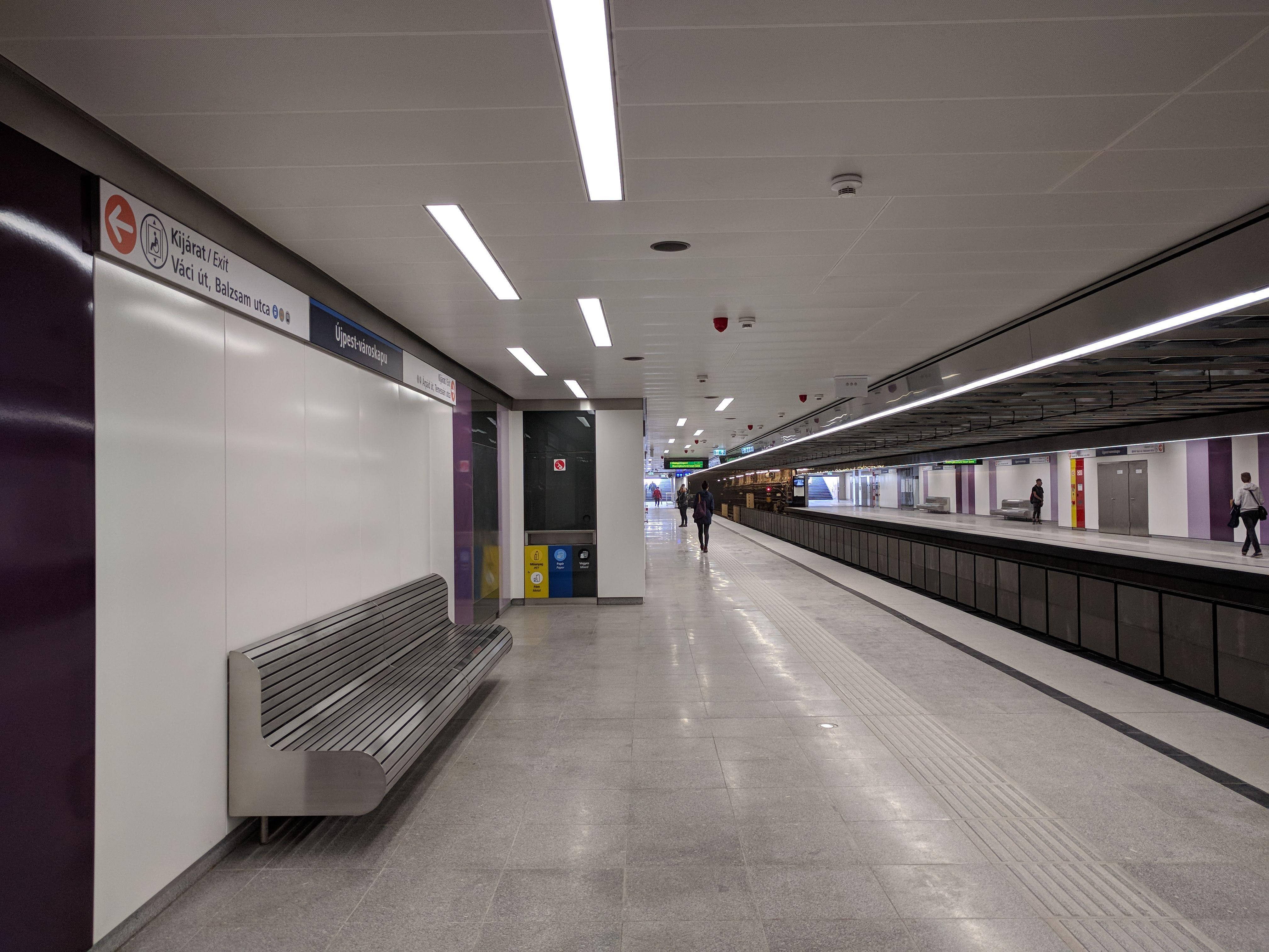 Újpest-városkapu meghatározó színeit nem kellett sokáig keresni. Az állomás visszafogott, mértéktartó lett, szerintem jól sikerült. A lila-fehér fém falburkolathoz fehér fém álmennyezet társul, a világítás pedig az álmennyezetben kapott helyet.