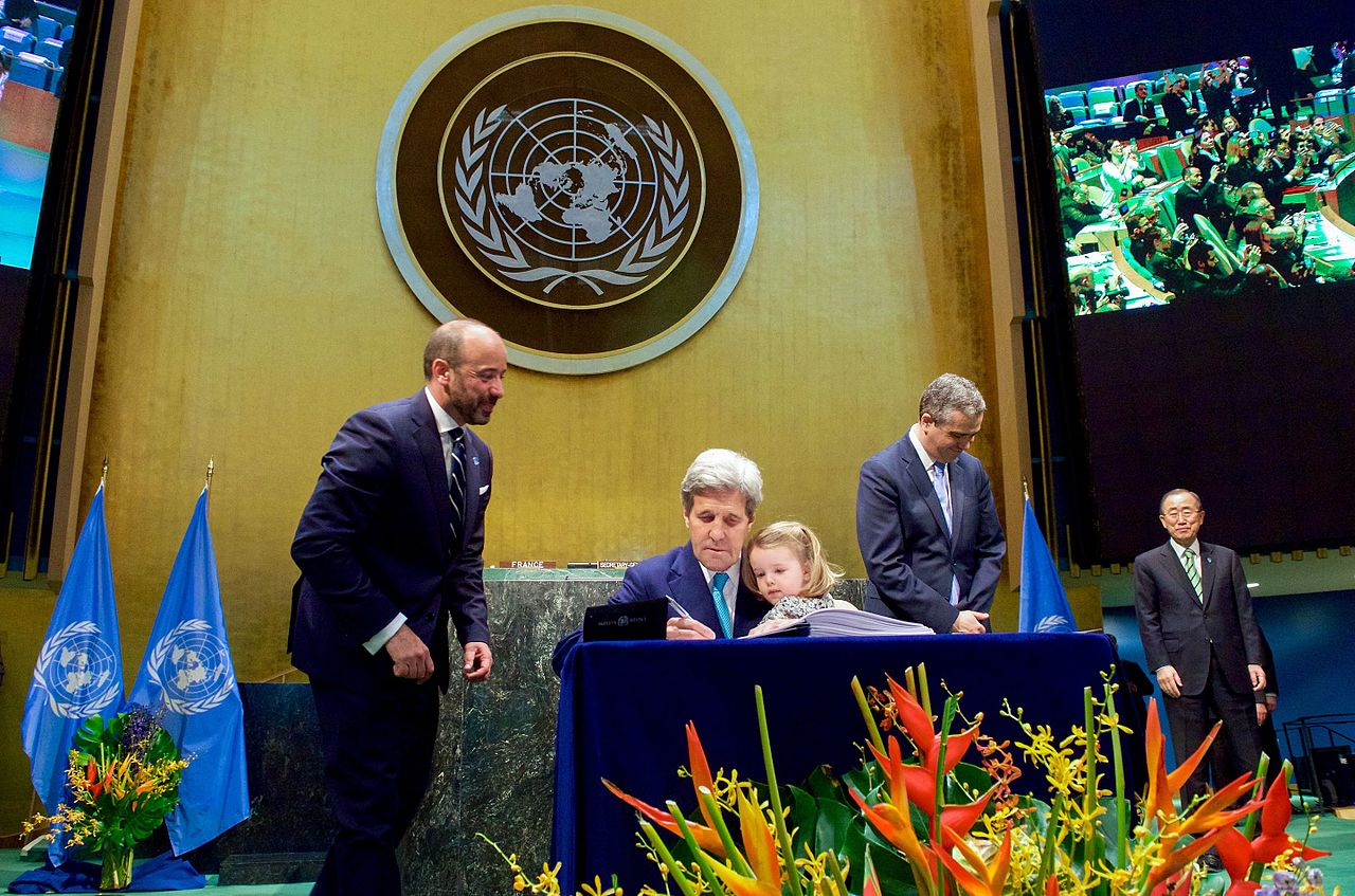 secretary_kerry_holds_granddaughter_dobbs-higginson_on_lap_while_signing_cop21_climate_change_agreement.jpg
