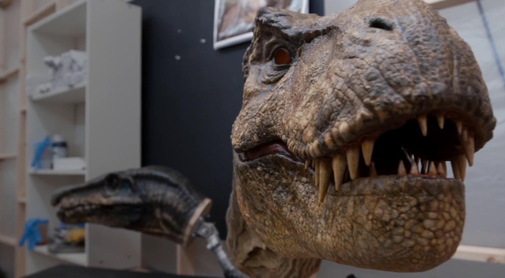 A Tyrannosaurus rex aprólékosan kidolgozott mellszobra mögött a Baryonyx feje látható