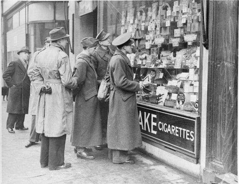 Czech soldiers and airmen look in the window of a tobacconist's shop at a display of cigarettes and tobacco, somewhere in London in 1940..jpg