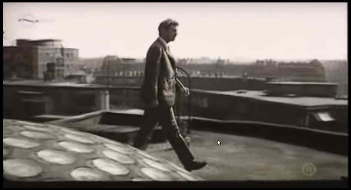 A nyomozót alakító főszereplő a tetőn, a lépcsőház üvegbetétes felülvilágítója mellett. Forrás: A gyilkos a házban van c. film (1971)