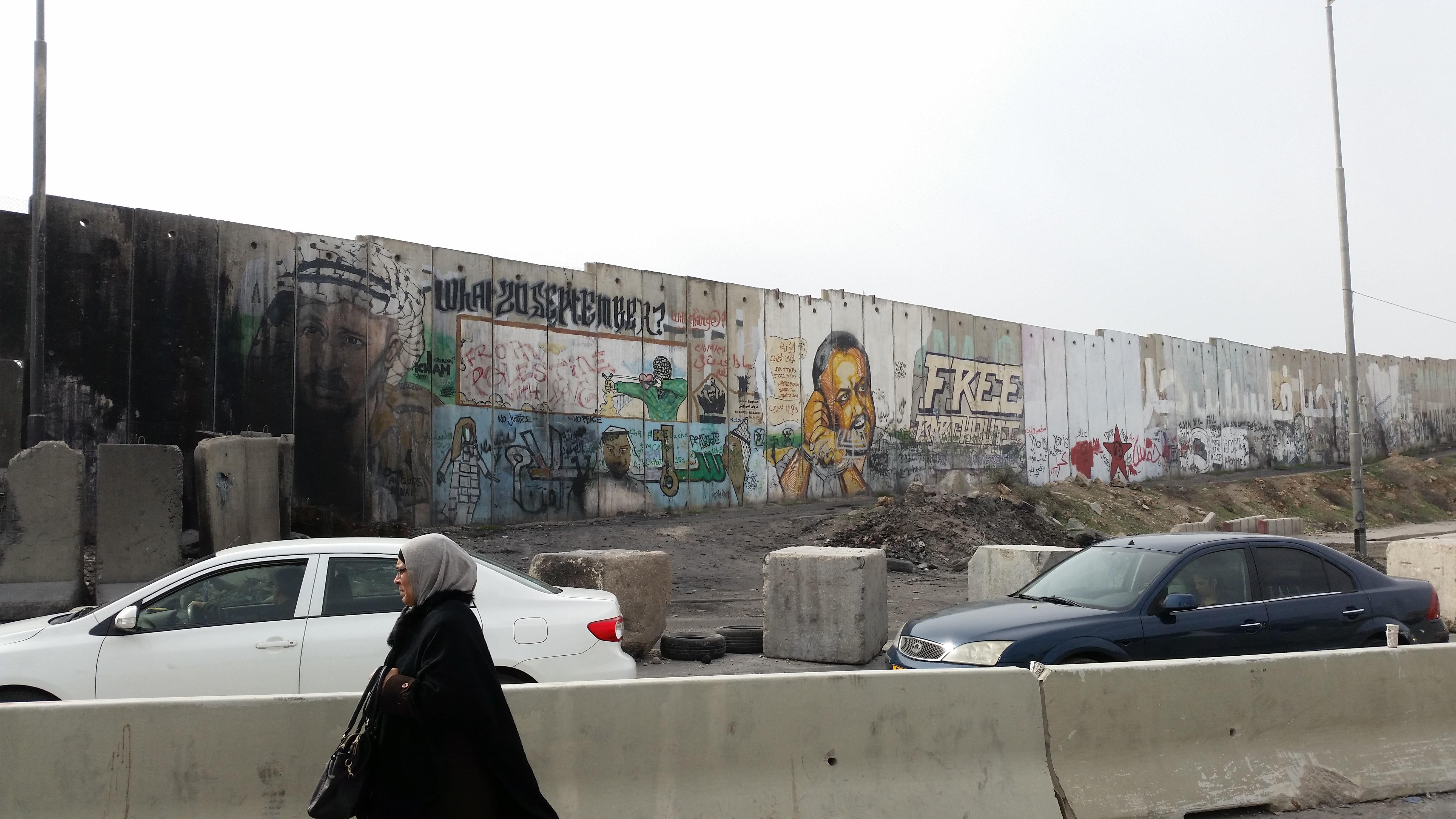 Fal Kalandiánál, a Ramallah és Jeruzsálem közötti fő ellenőrző pontnál. A legtöbb helyen a fal palesztin oldalán képekkel és festett feliratokkal üzennek a palesztinok.