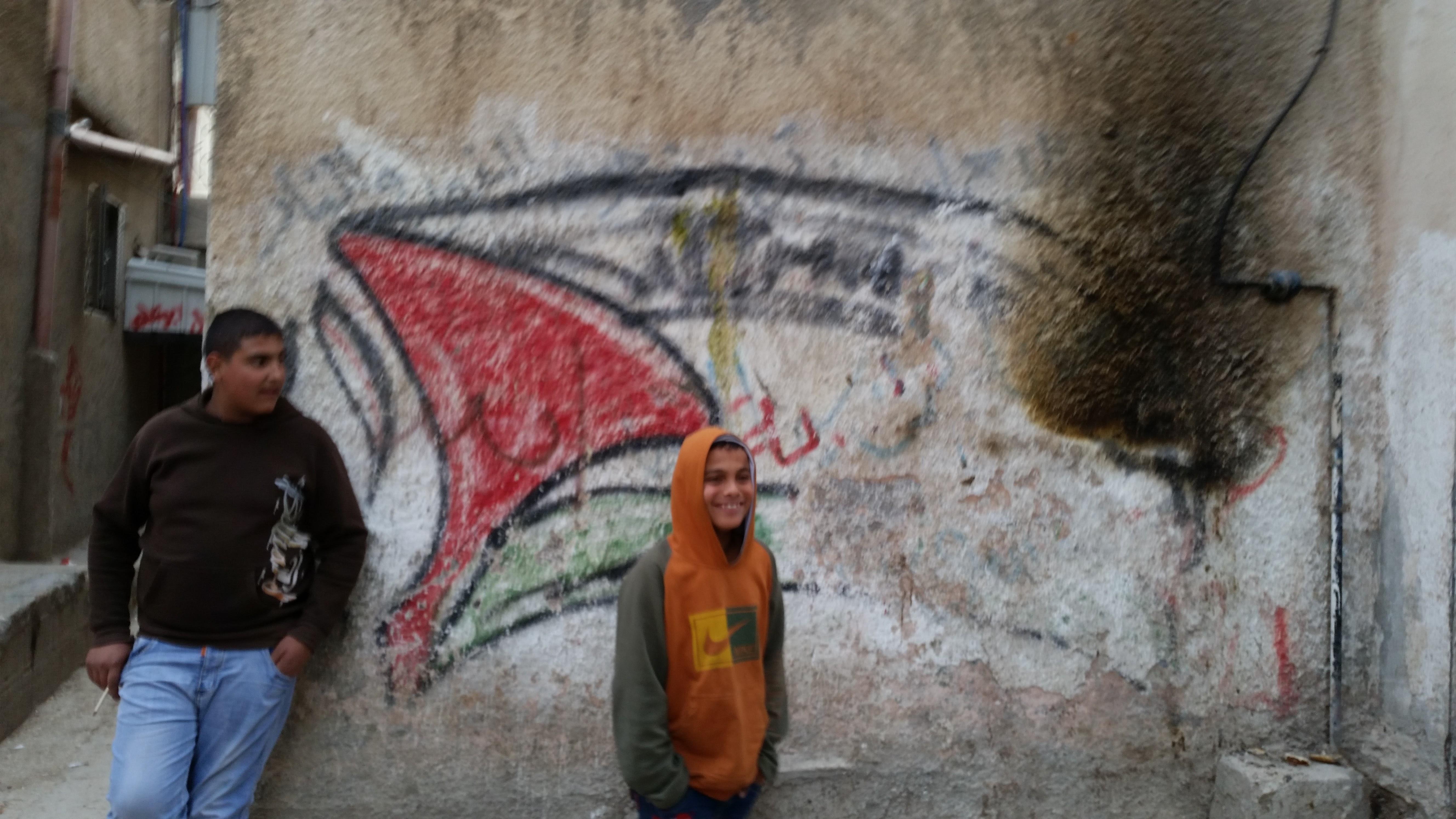 Gyerekek egy ház falára festett palesztin zászló előtt a menekülttáborban.<br />