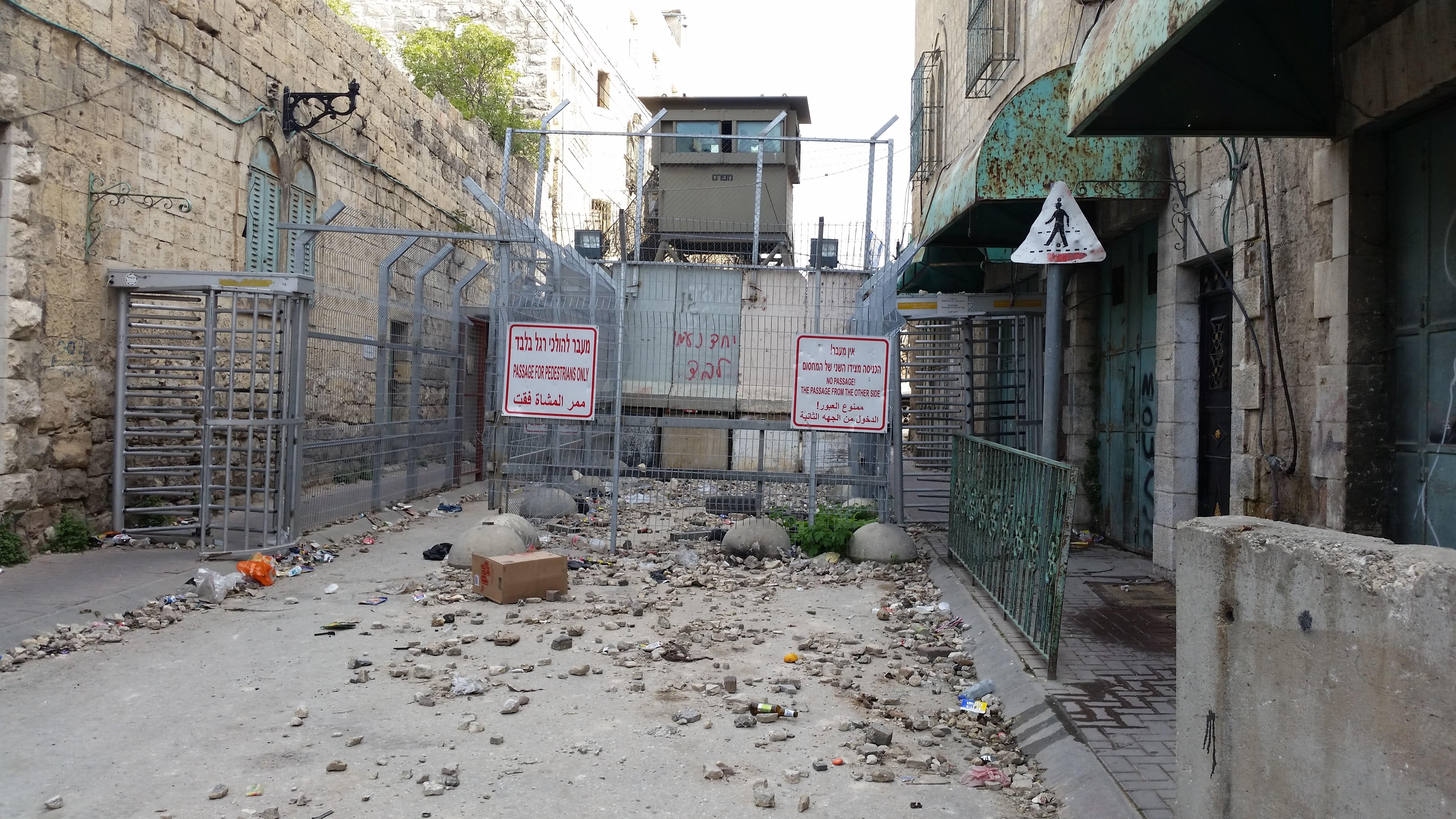 Ellenőrző pont Hebron belvárosában, az Al-Shuhada utcán, az izraeli katonaság lezárta az utcát a palesztin lakosok előtt. Régen ez volt a fő piaci utca, ma már nem lehetnek itt nyitva palesztin boltok.<br />