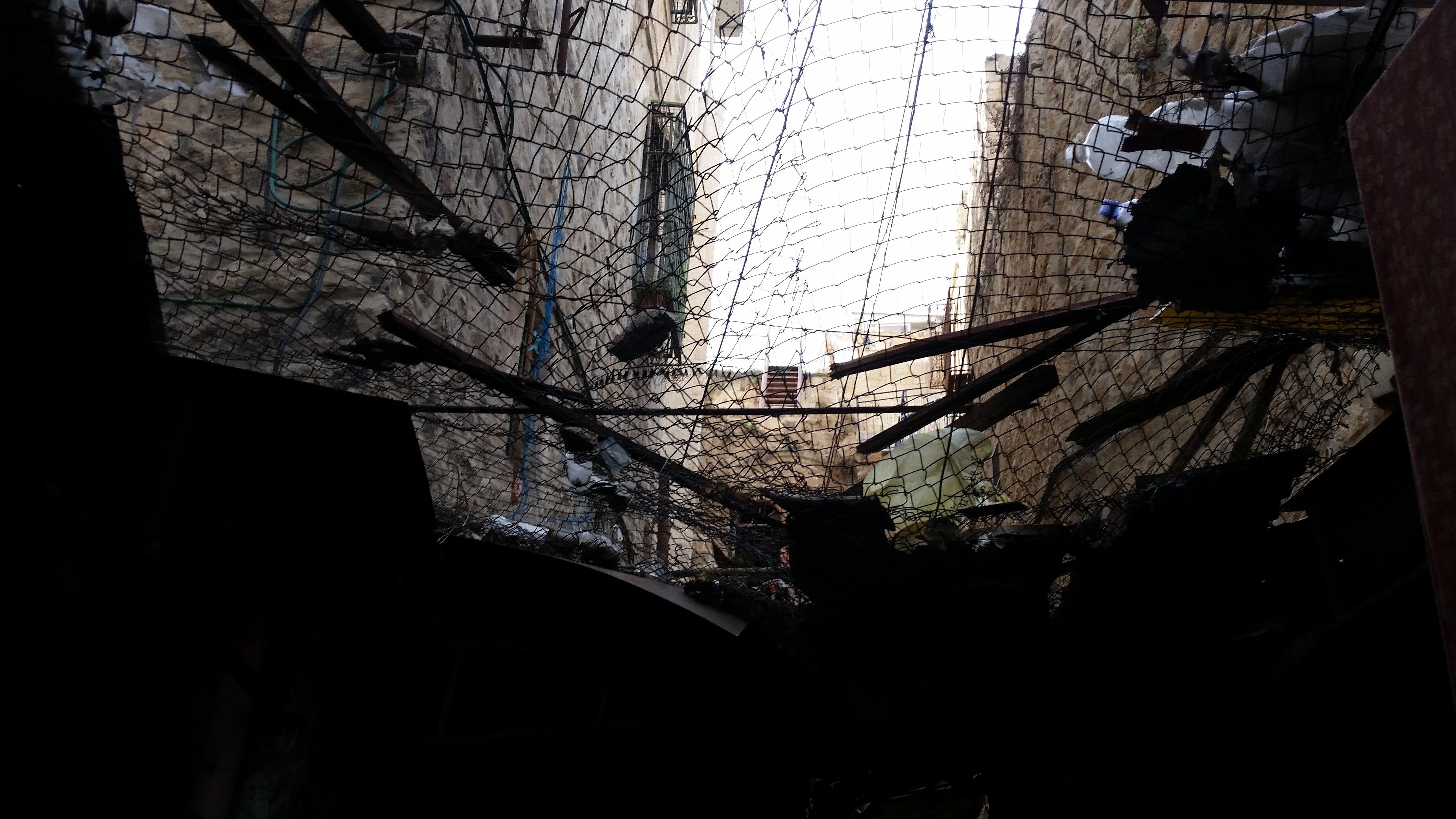 A még működő palesztin piac részen, háló az utca felett, hogy megvédje őket a fejükre hulló szeméttől, amit néhány izraeli lakos dobál ki az épületek ablakán.<br />