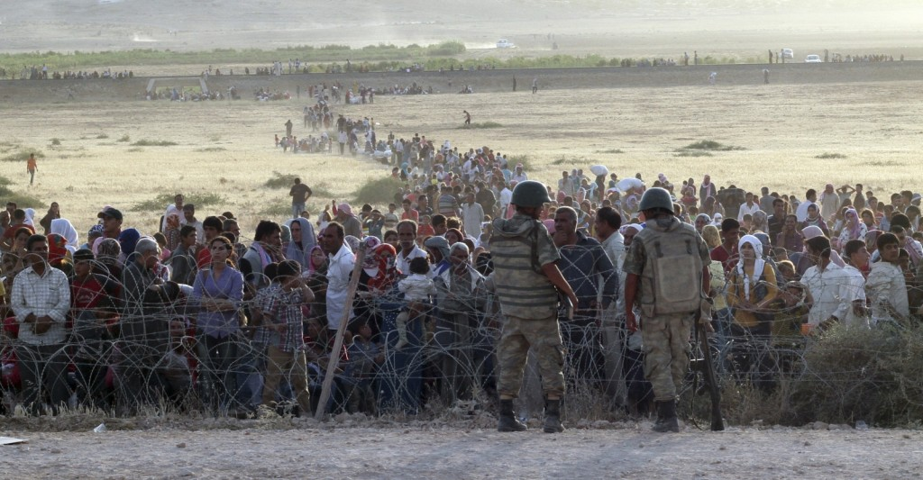 turkish-soldiers-stand-guard-syrian-refugees-wait-behind-border-fences-1024x533.jpg