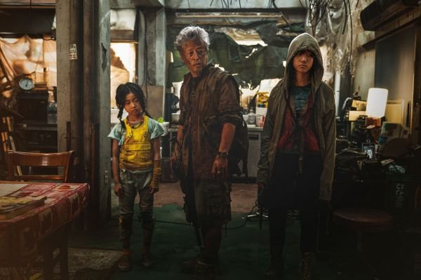 A kis Yoo-jin (Lee Ye-Won, balra) nővérével, Joon-yivel (Lee Re, jobbra) és a habókos nagyapjukkal (Kwon Hae-Hyo) szintén a menekülésen ügyködnek